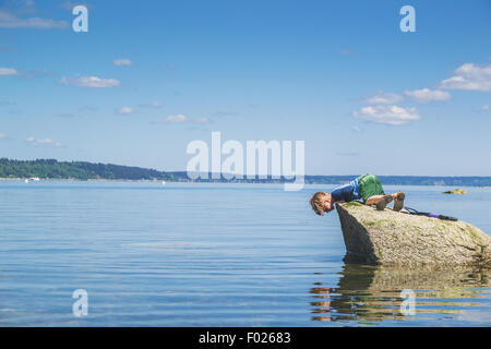 Boy on a rock looking down at his reflection in the sea - Stock Photo