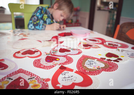Young boy writing out valentine cards - Stock Photo