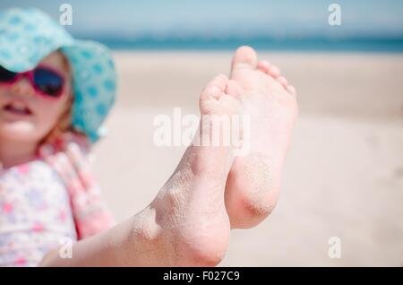 Girl showing off her sandy toes on the beach - Stock Photo