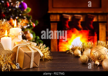Christmas decorations, a gift and candles in front of a fireplace. A fire is burning in the fireplace. - Stock Photo