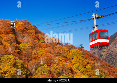 A cable car moving up a mountain covered in bright autumn colours. Photographed at the Akechidaira Ropeway near - Stock Photo