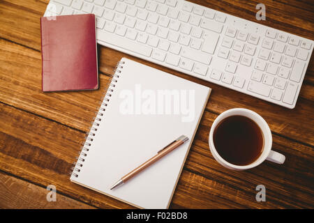 Pen on notepad next to cup of coffee passport and keyboard - Stock Photo