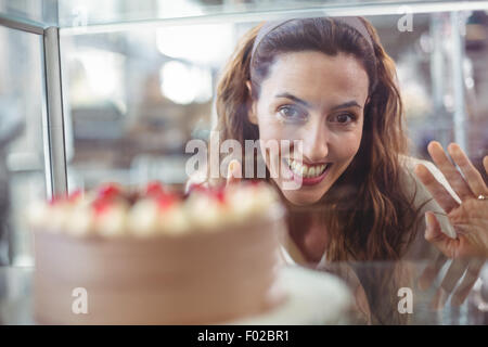 Pretty brunette looking at chocolate cake through the glass - Stock Photo