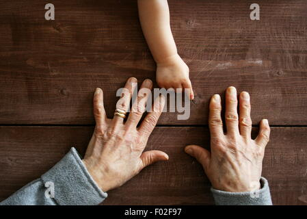 Baby boy's hand pointing at grandmother's hands - Stock Photo