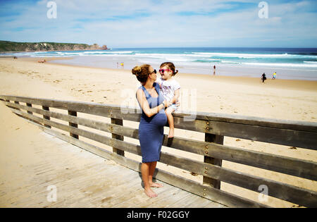 Pregnant woman at beach with her daughter - Stock Photo
