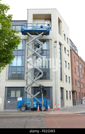 A small hydraulic scissor lift work platform accessing external surface of low rise building in Paisley, Renfrewshire, - Stock Photo