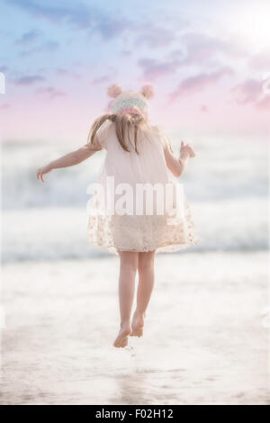Rear view of a girl jumping in the waves at the beach - Stock Photo