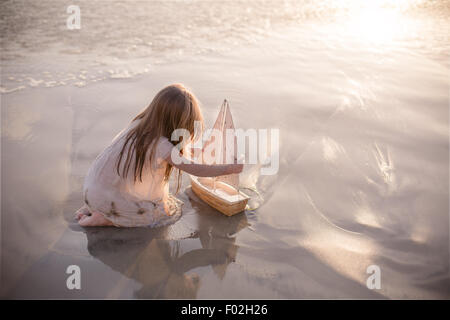 Girl sitting on the beach playing with a boat at sunset - Stock Photo
