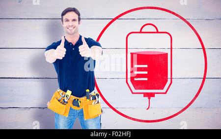 Composite image of man wearing tool belt while showing thumbs up sign - Stock Photo