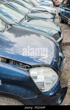 Scrap accident damaged cars or automobiles in a junk yard waiting for recycling - Stock Photo