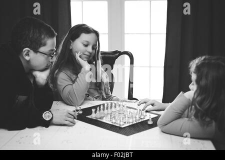 Three children playing a game of chess - Stock Photo