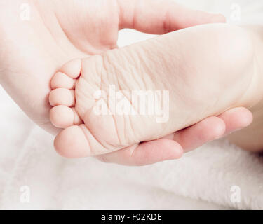 A woman's hand holding a newborn baby feet - Stock Photo