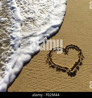 Heart shape drawn in the sand on a beach - Stock Photo