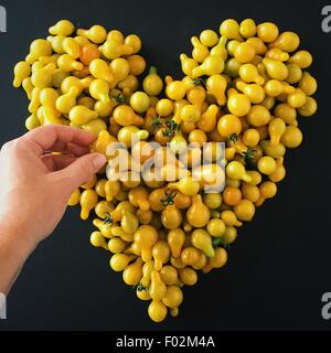 Hand making a heart shape with cherry tomatoes - Stock Photo