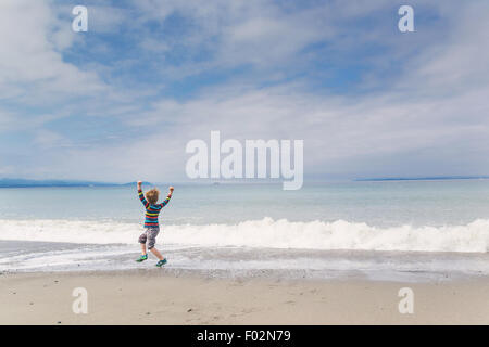Boy playing on beach - Stock Photo