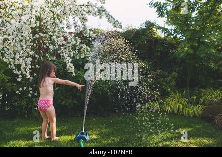Girl playing with hosepipe in the garden - Stock Photo
