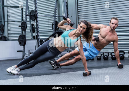 Muscular couple doing side plank - Stock Photo