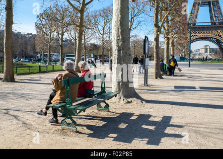 Two elderly women sitting on a bench by Eiffel Tower in winter, Paris - Stock Photo
