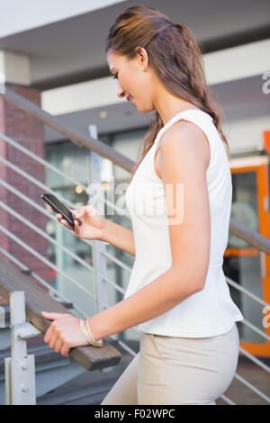 Smiling woman going upstairs while using her smartphone - Stock Photo
