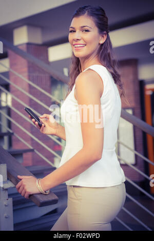 Portrait of smiling woman going upstairs while using her smartphone - Stock Photo