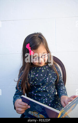 Five year old girl reading book - Stock Photo