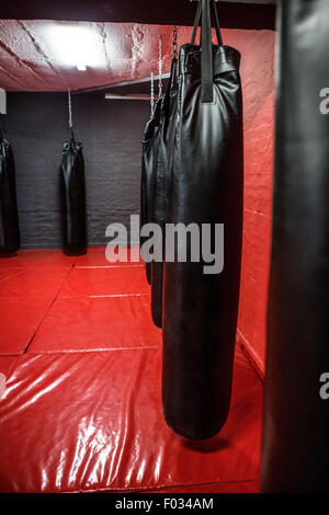 Punching bags in red boxing area - Stock Photo