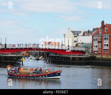 Decommissioned lifeboat leaving Whitby harbour to take tourists on a boat trip, with red bridge in the background. - Stock Photo