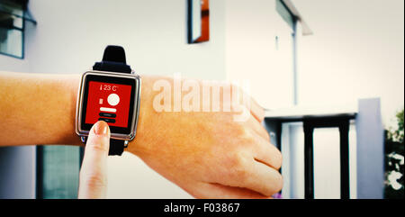 Composite image of smartwatch on wrist - Stock Photo