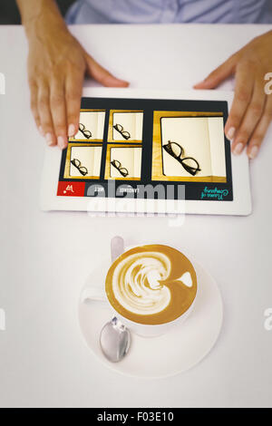 Composite image of close-up of digital tablet and coffee on table - Stock Photo