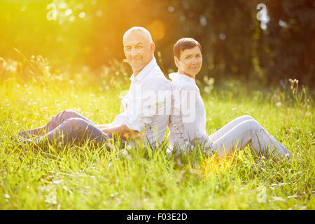 Happy senior couple relaxing on vacation in summer on a meadow - Stock Photo