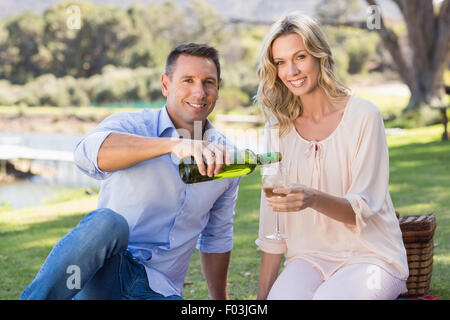 Portrait of smiling couple sitting and pouring wine in glass - Stock Photo