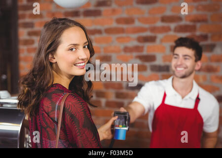 Smiling woman handing a pin terminal - Stock Photo
