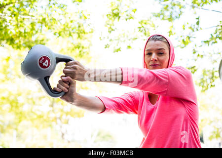 A pretty woman in a pink outfit doing exercise with a weight - Stock Photo