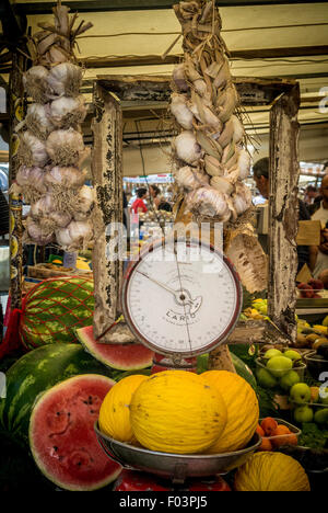 Honeydew melons displayed on old fashioned weighing scales at Campo de' Fiori outdoor food market in Rome., Italy. - Stock Photo