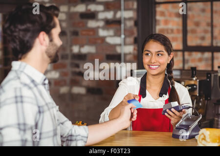 Customer handing a credit card to the waitress - Stock Photo