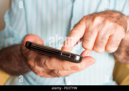 closeup of an old caucasian man sitting in an armchair uses a smartphone - Stock Photo