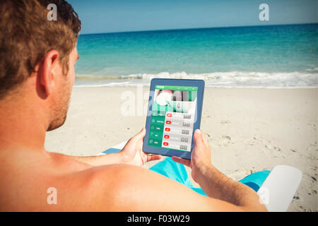 Composite image of man using digital tablet on deck chair at the beach - Stock Photo