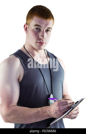 Fit personal trainer writing on clipboard - Stock Photo