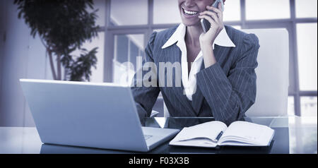 Businesswoman on call and using her laptop - Stock Photo