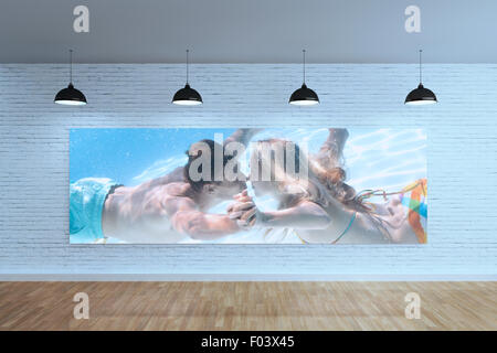 Composite image of cute couple kissing underwater in the swimming pool - Stock Photo