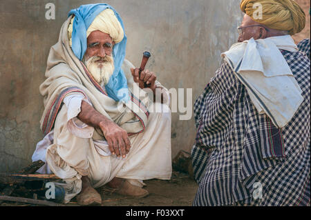Two aging men dressed traditionally in turbans smoke a clay pipe at the end of the day's camel trading. Stock Photo