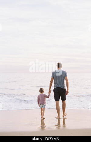 Man standing on a sandy beach by the ocean, holding his young daughter's hand. - Stock Photo