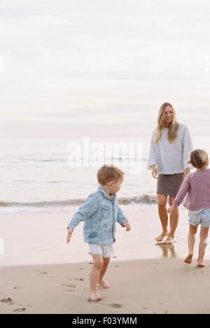 Woman playing with her son and daughter on a sandy beach by the ocean. - Stock Photo