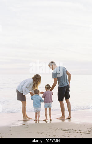 Couple playing with their son and daughter on a sandy beach by the ocean. - Stock Photo
