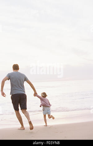 Man playing on a sandy beach by the ocean, holding his young daughter's hand. - Stock Photo