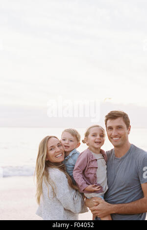 Couple standing with their son and daughter on a sandy beach by the ocean, looking at camera, smiling. - Stock Photo
