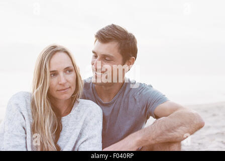 A couple sitting close on a beach, a man and woman with their arms around each other and heads together. - Stock Photo