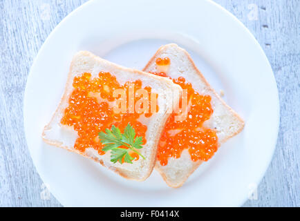 salmon caviar and bread on a table - Stock Photo