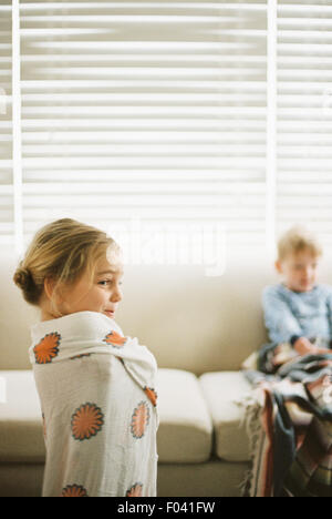 Young girl wrapped in a towel and a young boy sitting on a sofa. - Stock Photo
