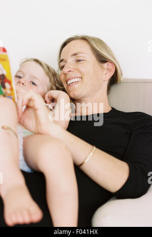 Woman sitting on a sofa, holding a book, reading to her daughter. - Stock Photo